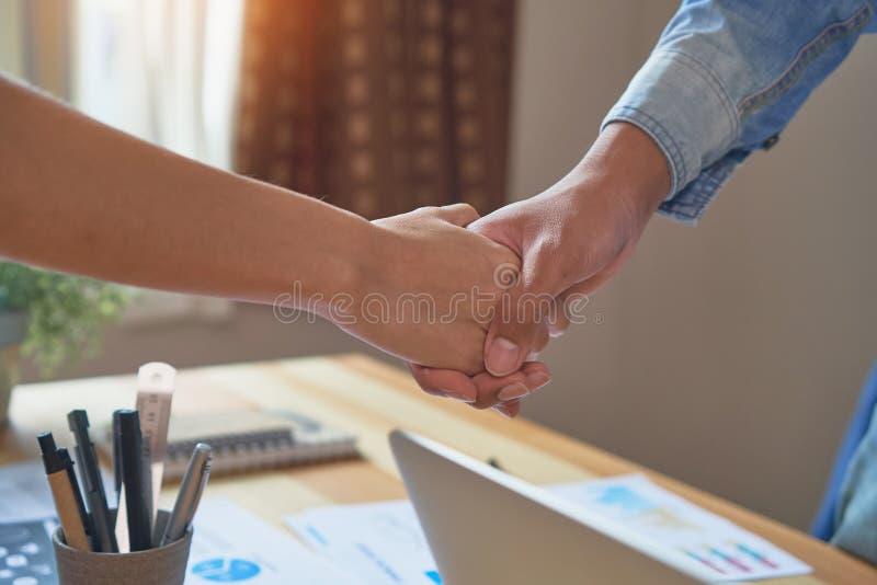 Mãos comum de dois homens de negócios após ter negociado um acordo bem sucedido do negócio, e o aperto de mão junto fotografia de stock royalty free