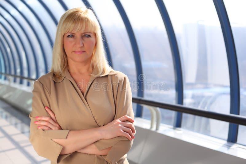 Mãos cruzadas da mulher de negócios wih de meia idade sério fotos de stock royalty free