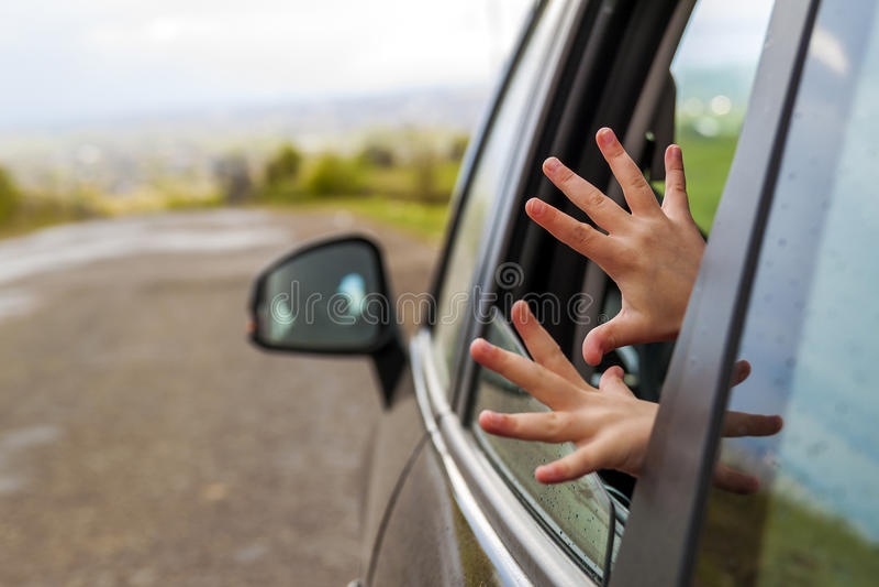 Mãos da criança em uma janela de carro durante o curso às férias imagens de stock royalty free