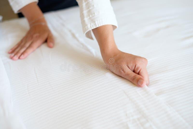 Mãos da empregada doméstica do hotel que fazem a cama imagens de stock royalty free