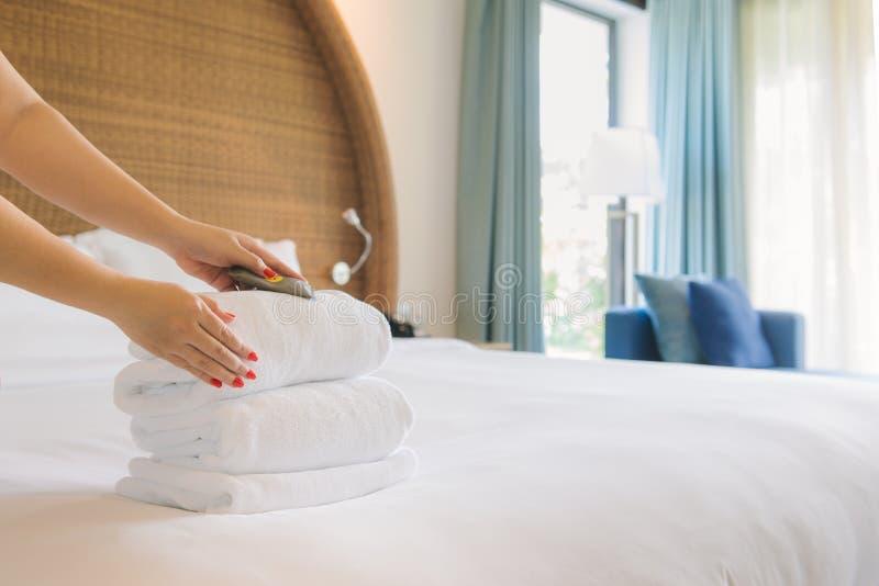 Mãos da empregada doméstica do hotel que trazem toalhas frescas à sala fotos de stock