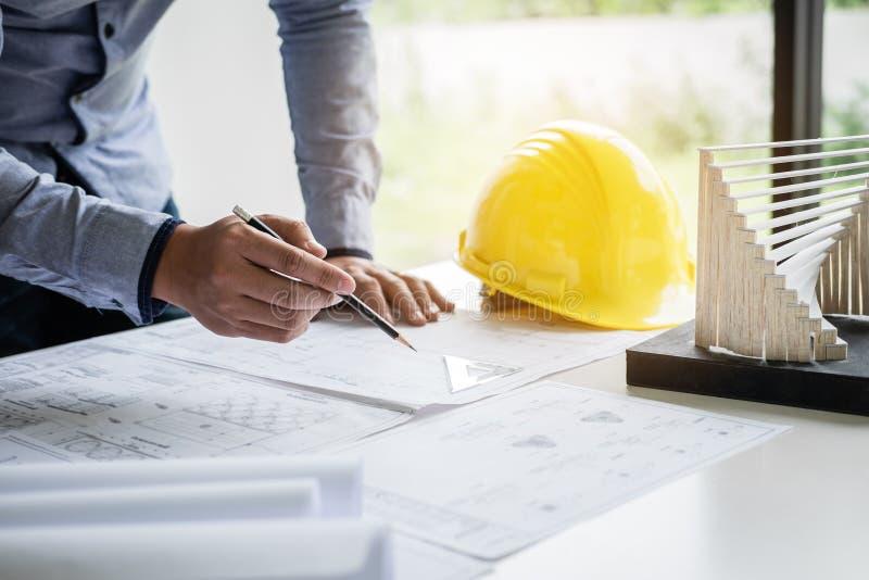 Mãos da engenharia ou do arquiteto de construção que trabalham na inspeção do modelo no local de trabalho, ao verificar o desenho imagem de stock