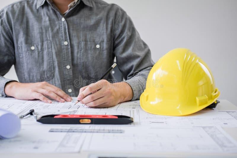 Mãos da engenharia ou do arquiteto de construção que trabalham na inspeção do modelo no local de trabalho, ao verificar o desenho fotografia de stock
