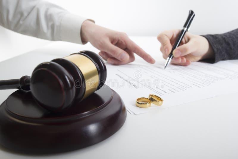 Mãos da esposa, decreto do marido do divórcio de assinatura, dissolução, cancelando a união, originais da separação legal, arquiv imagem de stock