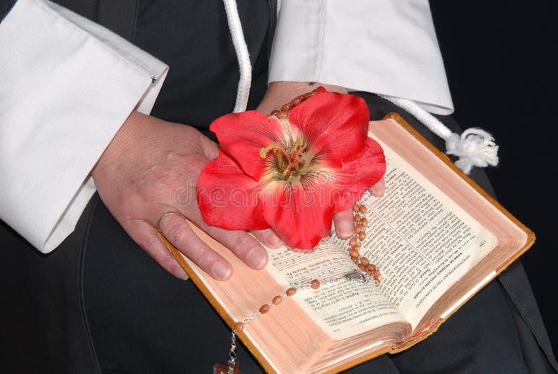 Mãos da freira com a flor na Bíblia fotografia de stock royalty free