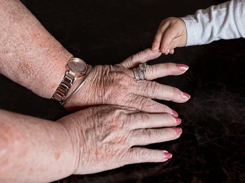 Mãos da grande avó e de seu grande neto do bebê imagem de stock