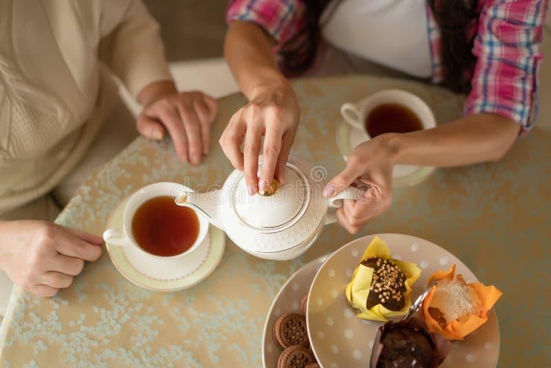Mãos da jovem mulher com chá de derramamento do bule branco da porcelana no copo de sua mãe superior foto de stock royalty free