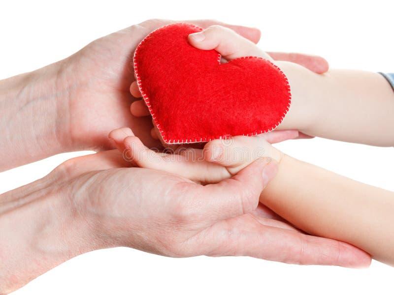 Mãos da mãe e do filho que guardam o símbolo do coração imagens de stock royalty free