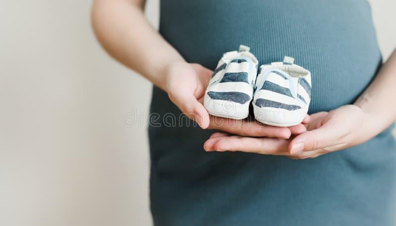 Mãos da mãe que guardam sapatas para o bebê recém-nascido Barriga tocante da mulher gravida Gravidez feliz da mulher, maternidade imagem de stock