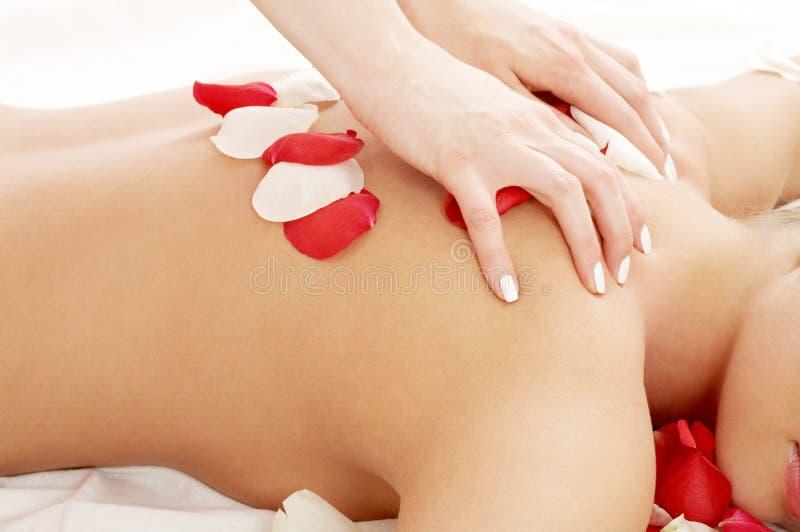 Mãos da massagem e pétalas cor-de-rosa imagens de stock royalty free