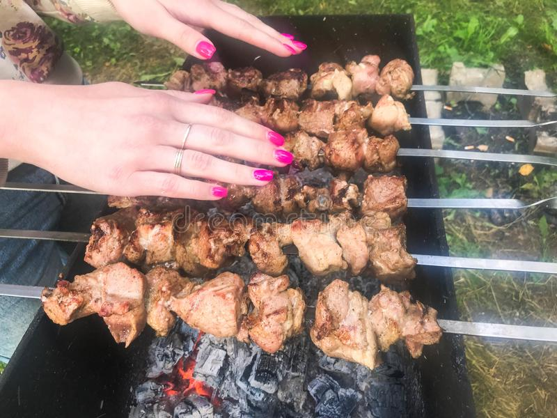Mãos da menina da mulher com um no espeto cor-de-rosa bonito das grades do tratamento de mãos em carvões e fumo natural na grade  fotos de stock