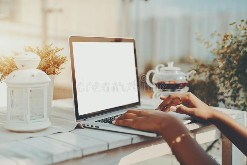 Mãos da menina preta que usa o portátil com molde vazio da tela fotos de stock royalty free