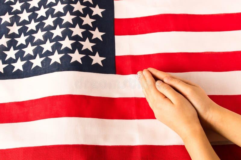 Mãos da menina rezando no fundo da bandeira americana O conceito do patriotismo imagens de stock royalty free
