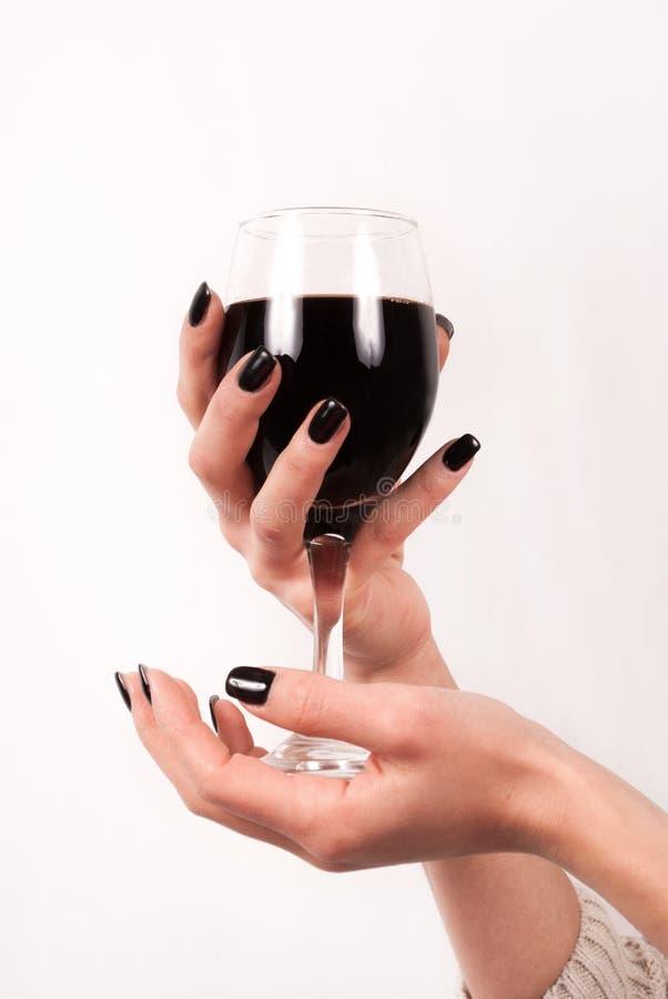 Mãos da moça com os pregos pretos que guardam de vidro com vinho tinto, fim acima foto de stock
