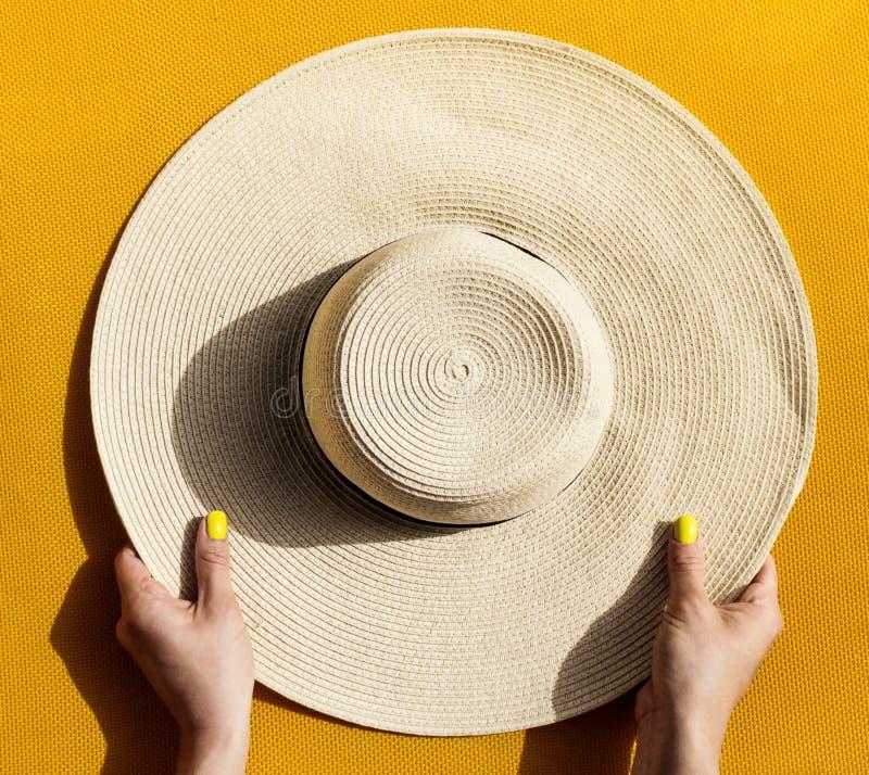 Mãos da moça que guardam o chapéu de palha no backgrou amarelo vibrante fotos de stock royalty free