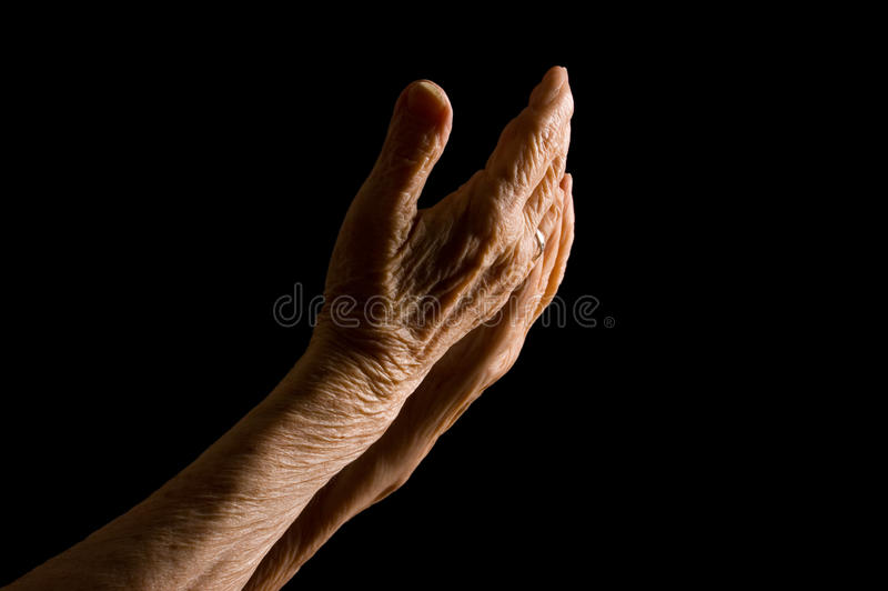 Mãos da mulher adulta em um fundo preto fotografia de stock royalty free