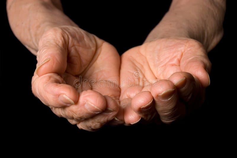Mãos da mulher adulta em um fundo preto imagens de stock royalty free