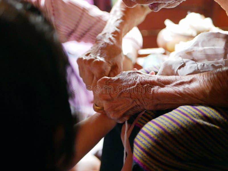 Mãos da mulher adulta que puxam que acenam uma corda branca Sai Sin após ter amarrado a em torno de suas mãos da neta - tradicion fotos de stock royalty free