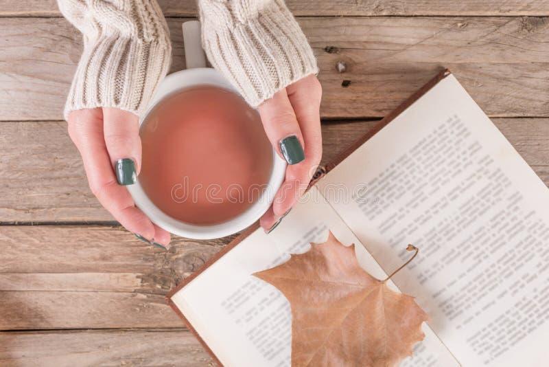 Mãos da mulher com a camiseta que guarda o copo do chá e o livro aberto com a folha caída seca imagem de stock