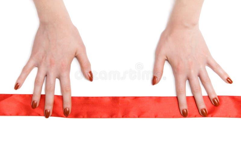 Mãos da mulher com fita vermelha fotografia de stock