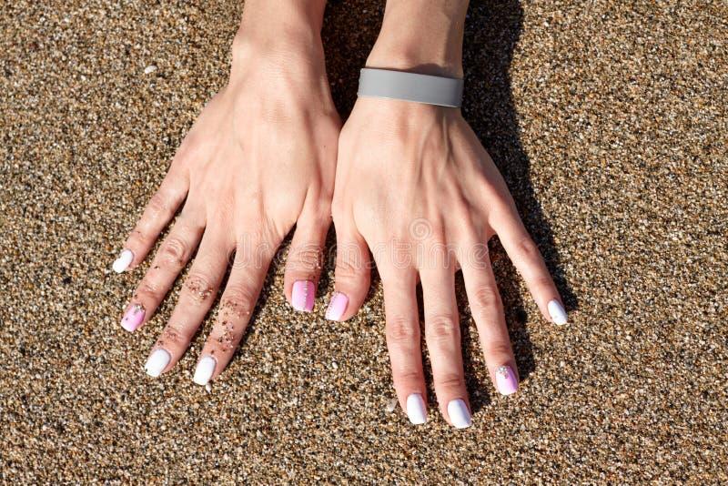 Mãos da mulher com os pregos bonitos na areia do mar foto de stock