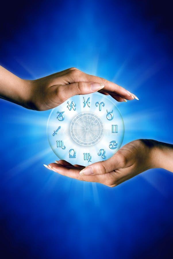 Mãos da mulher com símbolos do zodíaco e horóscopo como o conceito da astrologia sobre o fundo azul imagem de stock royalty free