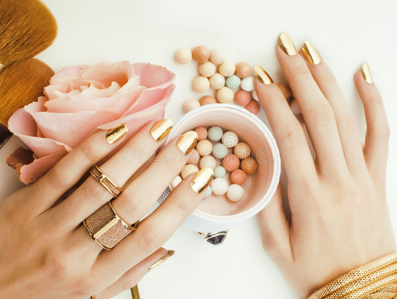 Mãos da mulher com tratamento de mãos dourado e muitos anéis que guardam escovas, material à moda, fim puro do maquilhador acima  imagens de stock
