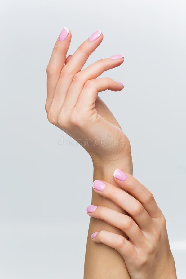 Mãos da mulher com tratamento de mãos francês fotografia de stock royalty free