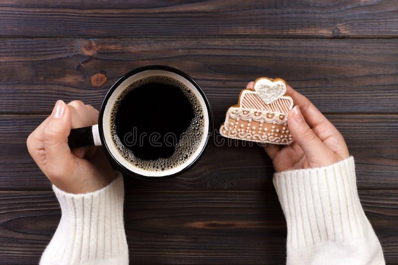 Mãos da mulher com a xícara de café com cookies imagens de stock royalty free