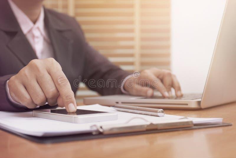 Mãos da mulher de negócio usando o cálculo esperto móvel do telefone e do portátil fotos de stock