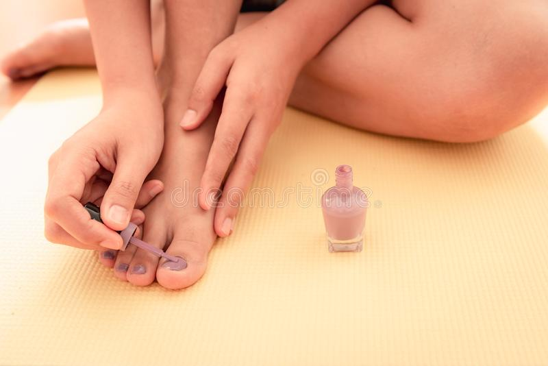 Mãos da mulher do close-up que estão sendo pintadas seus pés dos pregos foto de stock