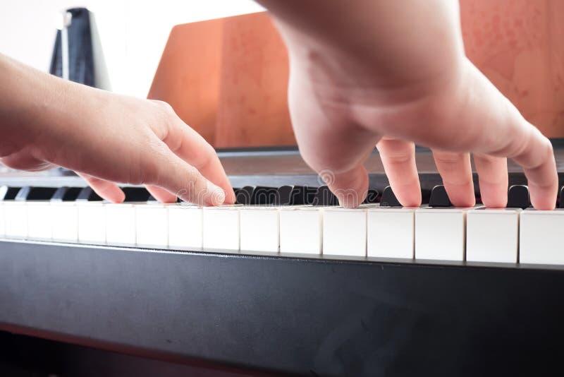 Mãos da mulher do close up que jogam o piano Fundo da música e da arte imagem de stock