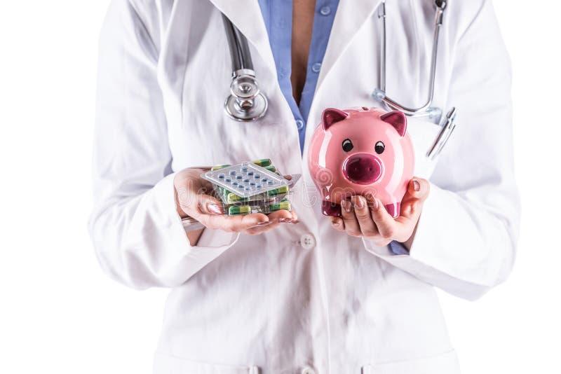 Mãos da mulher do doutor que guardam comprimidos e mealheiro imagem de stock