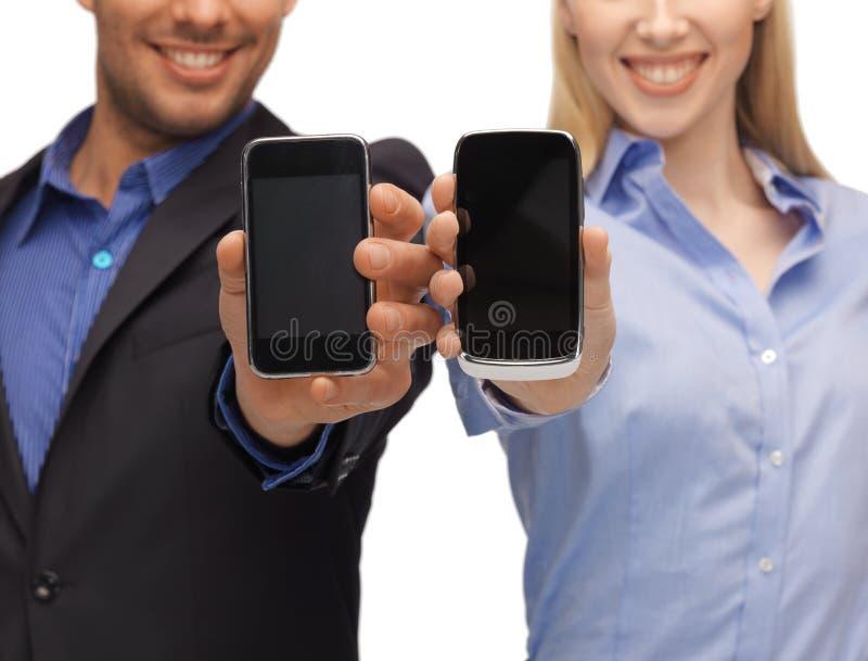 Mãos da mulher e do homem com smartphones imagens de stock royalty free