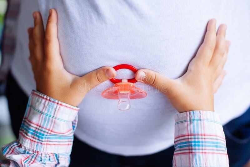 Mãos da mulher gravida e da sua filha nova que guardam o dum do bebê foto de stock