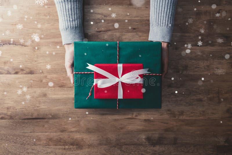 Mãos da mulher na camiseta cinzenta no presente de madeira b do Natal do givin da tabela imagens de stock royalty free