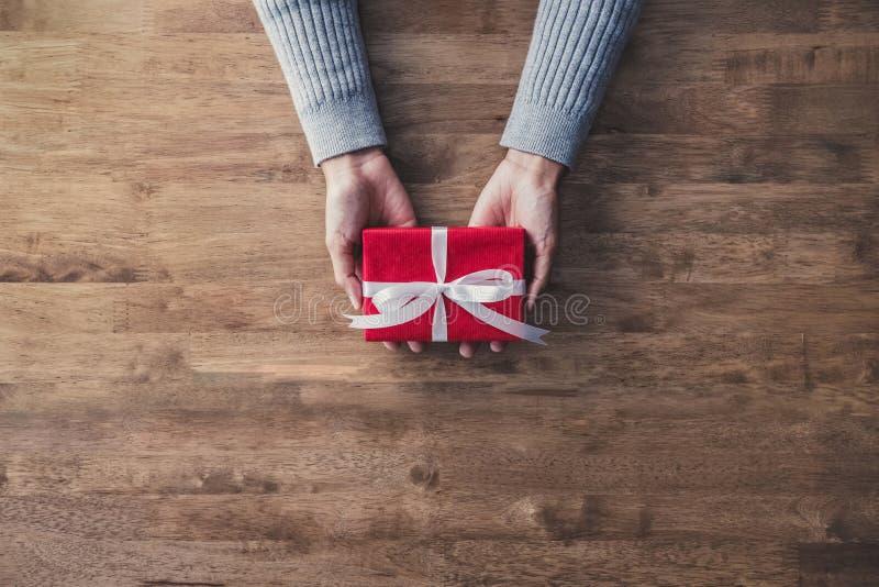 Mãos da mulher na camiseta cinzenta na tabela de madeira que dá a caixa de presente vermelha do Natal envolvida com fita branca imagem de stock