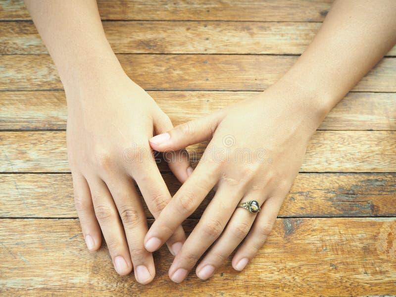 Mãos da mulher na tabela de madeira imagens de stock