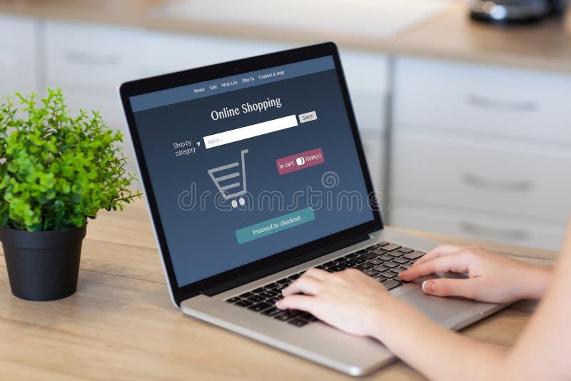 Mãos da mulher no portátil com compra em linha na tela imagens de stock royalty free