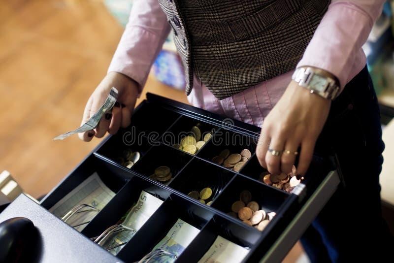 Mãos da mulher no registo de dinheiro fotografia de stock royalty free