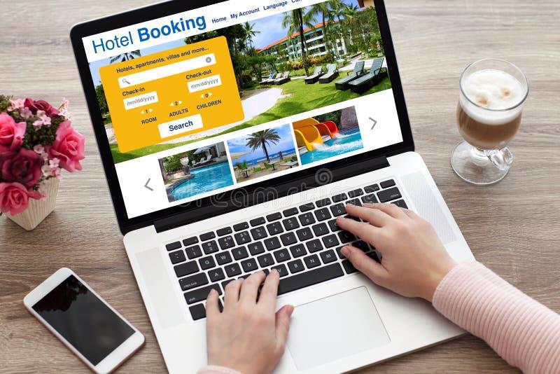 Mãos da mulher no teclado do portátil com o hotel em linha do registro da busca imagens de stock