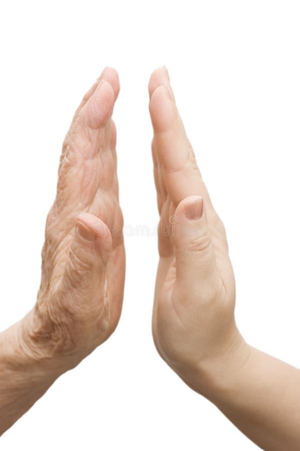 Mãos da mulher nova e das pessoas idosas fotografia de stock royalty free