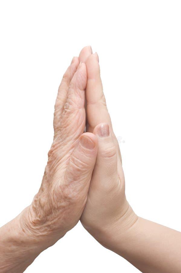 Mãos da mulher nova e das pessoas idosas fotografia de stock