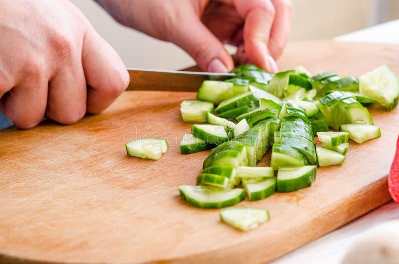 Mãos da mulher que cortam vegetais no fundo de madeira imagem de stock royalty free