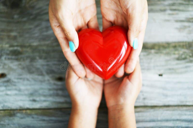 Mãos da mulher que dão um coração vermelho brilhante a sua filha, compartilhando do conceito do amor imagens de stock royalty free
