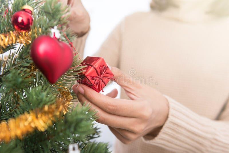 Mãos da mulher que decoram a árvore de Natal fotografia de stock