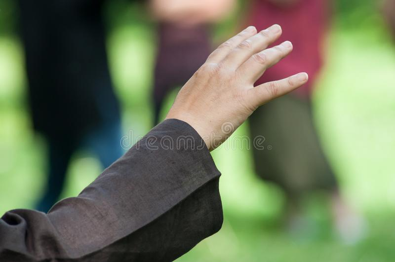 mãos da mulher que fazem o qui da TAI no parque urbano foto de stock royalty free