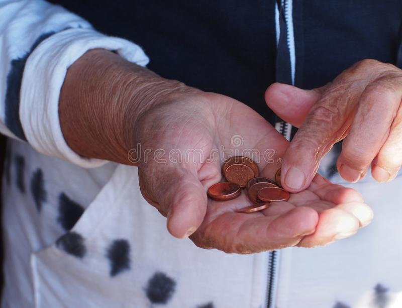 Mãos da mulher que guardam algumas moedas do euro Pensão, pobreza, problemas sociais e tema da senilidade imagem de stock