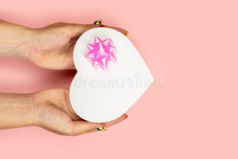 Mãos da mulher que guardam a caixa de presente com a curva cor-de-rosa isolada sobre o fundo cor-de-rosa Natal, ano novo, conceit imagens de stock