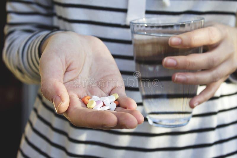 Mãos da mulher que guardam comprimidos da cor e um vidro da água Conceito da saúde foto de stock